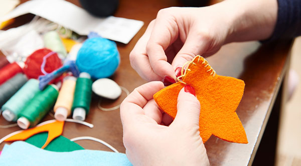 How To Sew By Hand? Sew a Star by hand, some needles and thread reels are on table