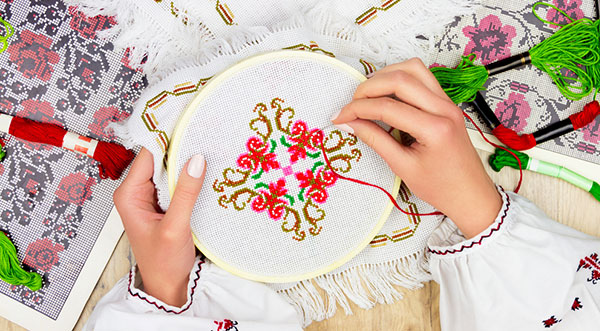 what is embroidery? Hand embroidery on white table cover with red thread