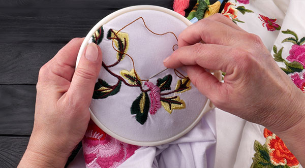 Girl do practice the basic stitching steps on embroidery hope with yellow and brown thread